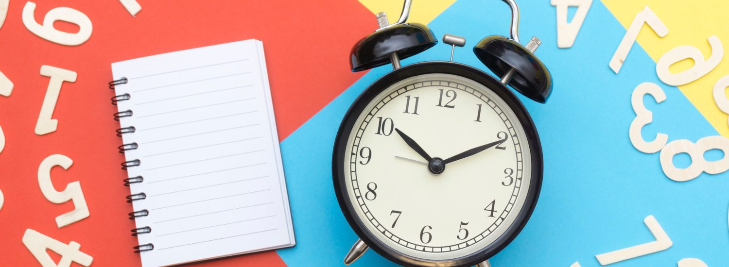 Alarm clock and notebook - start your office move planning early!