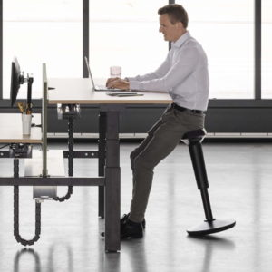 stand up stool in use at a standing desk