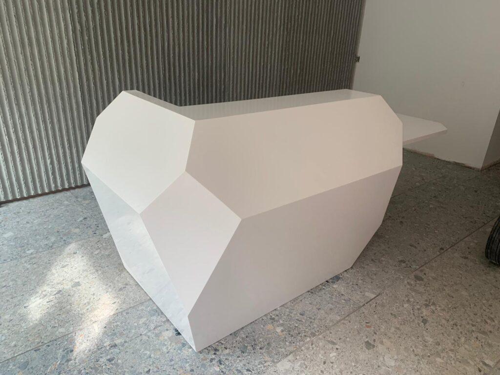 modern, geometric reception desk in Glacier White Corian